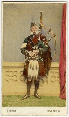 [Hand-colored carte-de-visite depicting a man playing a bagpipe]